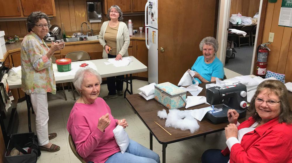 Five women sewing.