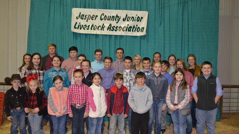 "About 30 young kids stand in front of a green curtain with a sign that says, ""Jasper County Junior Livestock Associations."""