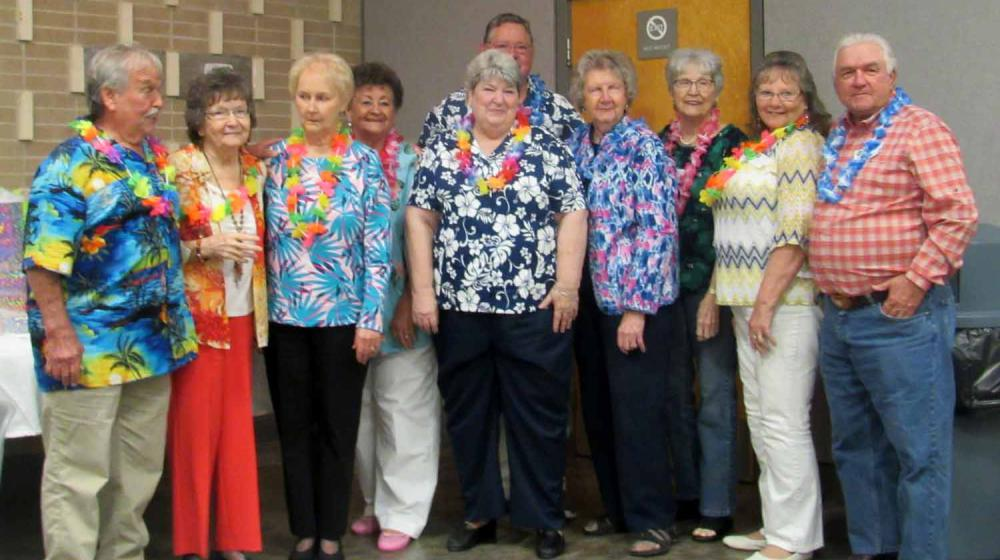 Ten men and women wearing vibrant shirts and multi-colored leis stand next to each other.