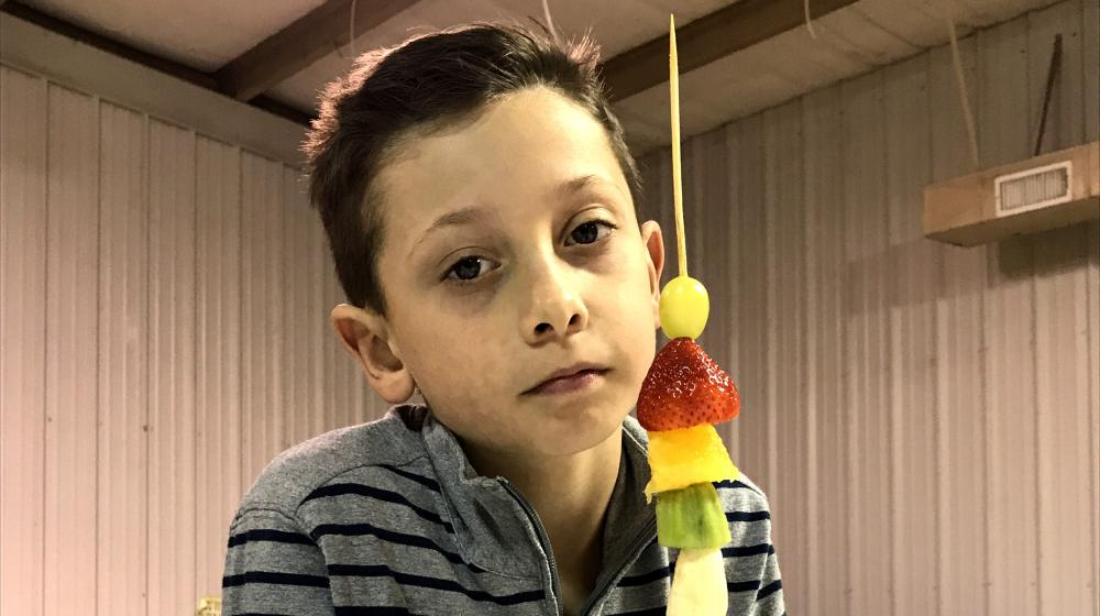 a boy with fruit on a skewer