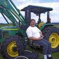 Chris Bell sits next to his tractor that has been equipped with a lift device and hand controls so he can operation it from his wheelchair. (Photo by Emily Knight/Mississippi State University Extension Service) See larger view.