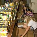 Mississippi State University students, from the front, Elisabeth Brooks, Patrisha Pham, Alessandra Pham and Joan DeSutter sort canned food into boxes for food pantries in Oktibbeha, Clay and Lowndes counties. (Photo by Marco Nicovich)