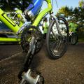 A close up shot of the gears and bottom of a fluorescent green bike parked in a parking lot.
