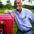 Smiling man in gingham dress shirt leans on a tractor