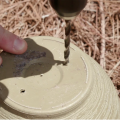 Fingers steady an upside-down flower pot as a drill bit pierces the bottom to make drainage holes.