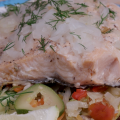 A steamed salmon filet sprinkled with onions and dill sits atop roasted vegetables.