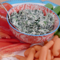 Spinach dip in a ceramic bowl centered on a plate surrounded by cut celery, baby carrots, and sliced red bell pepper.
