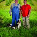 •	A man in overalls stands beside a man in a red T-shirt in front of a tree farm