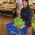 A woman in a grocery store holding a blue basket filled with produce like leafy green lettuce.