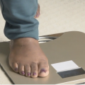 A close up picture of a person's foot stepping on a scale.