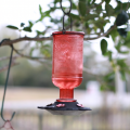 A red bird water feeder hanging on a tree.