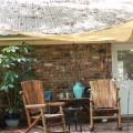 Two wooden chairs on a porch underneath a tan shade sail.