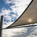 A shade sail with cloudy blue sky.
