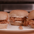 Three small sandwiches made with whole wheat slider buns, shredded chicken, and barbecue sauce on a white plate.