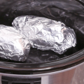 Foil wrapped potatoes in a slow cooker.