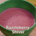 A pink blended raspberry dessert in a green cup.