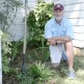 A man kneels in a flower bed next to some plants.