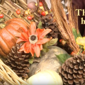 Close-up of a fall decorative basket with pine cones, pumpkins, gourds and artificial flowers and grasses.