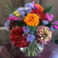 Orange, red, pink, purple, and yellow flowers are arranged in a glass bowl that sits atop a small, red table.