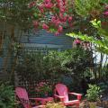 The Adirondack chair is a style of furniture that has stood the test of time and reached heirloom status. These hot pink chairs and matching table are flanked by tall crape myrtles of a similar color.