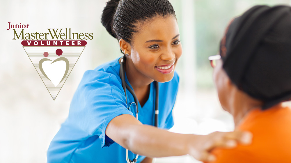 An image of a young woman volunteering in health setting. The Junior Master Wellness Volunteer logo is embedded.