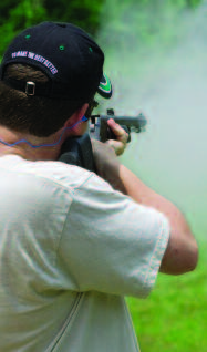 A young man wearing a white shirt and black cap, aims and shoots a muzzleloader causing smoke to fill the air.
