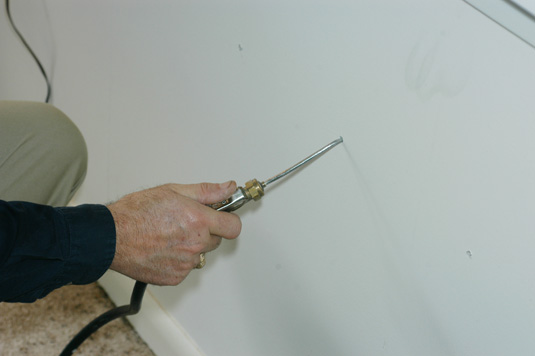 Termiticide foam is being injected into a wall void.  The foam has a consistency similar to shaving cream.