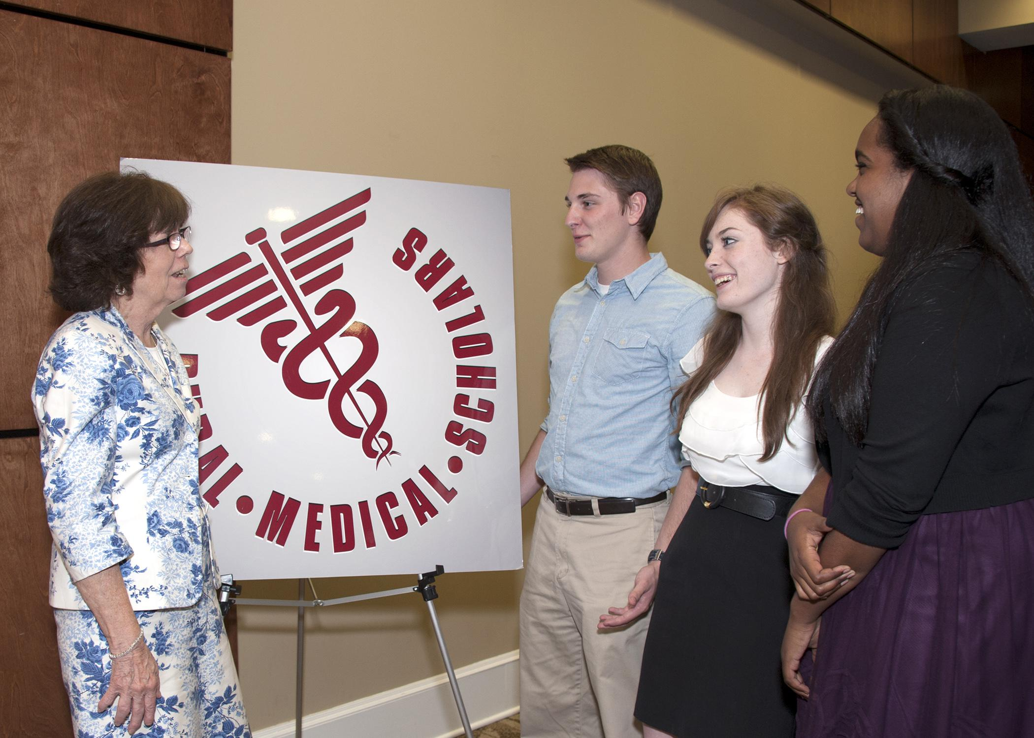 An instructor and three students have a discussion in front of a Rural Medical Scholars sign.